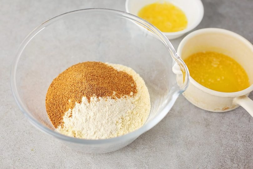 mixing bowl with flour, sugar and the small saucepan with melted butter plus small dish with whisked egg