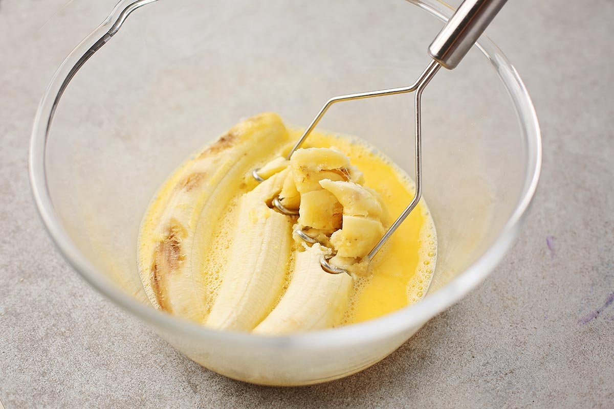 glass bowl with mashed bananas, butter, and eggs