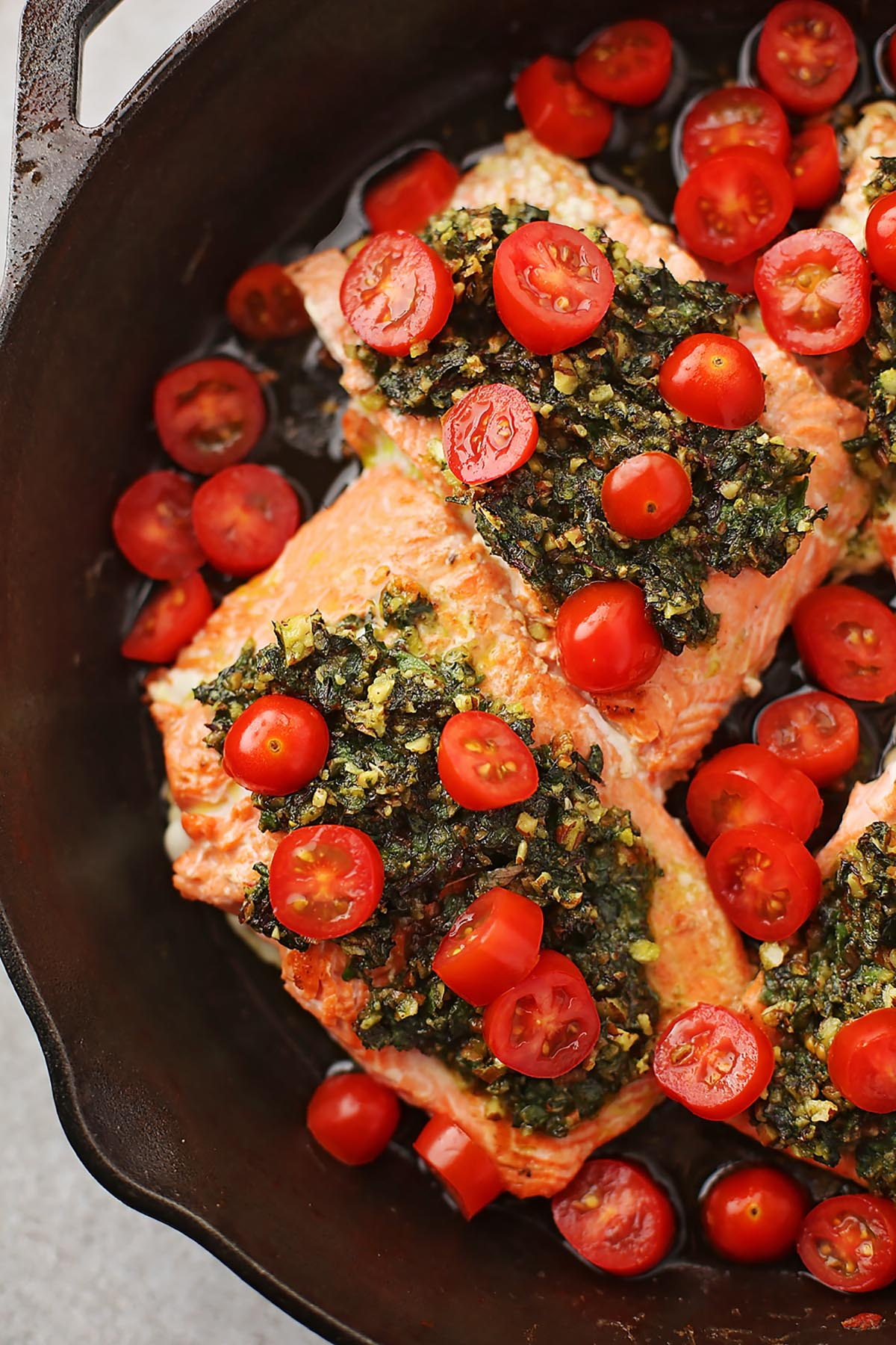 close up shot of cast iron pan with salmon topped with red tomatoes and green pesto sauce