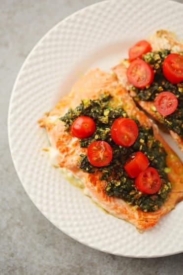 white plate with cooked salmon slice topped with green sauce and bright red grape tomatoes