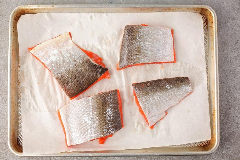four pieces of raw sliced salmon