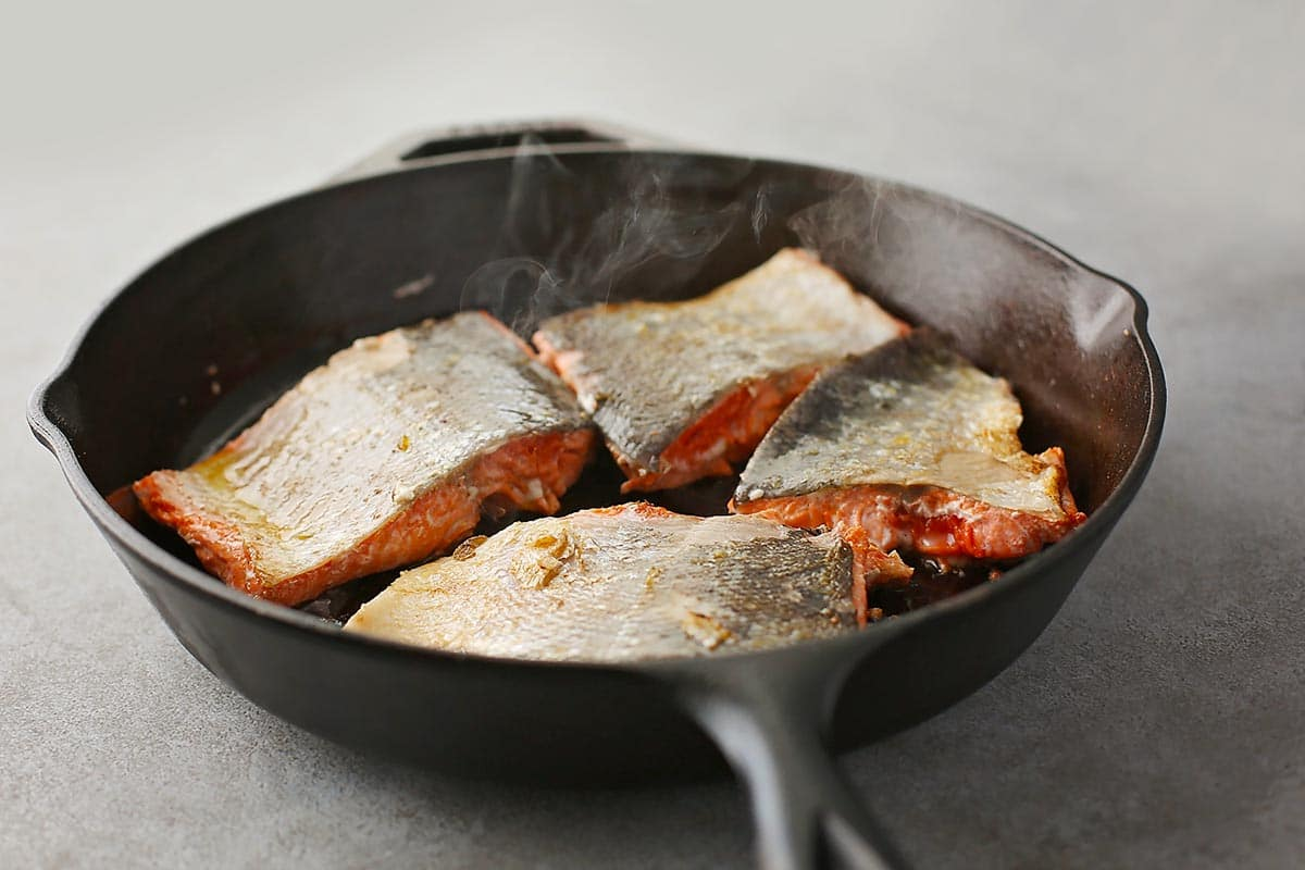 cast iron pan with slices of salmon inside