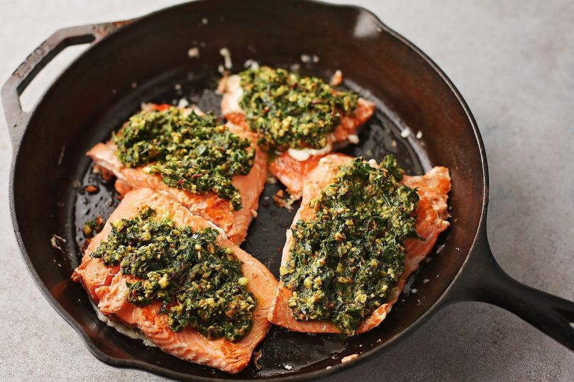 cast iron pan with cooked slices of salmon topped with pesto sauce