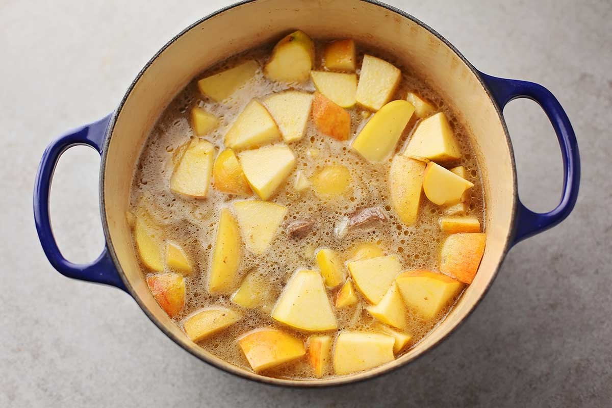 dutch oven filled with apple slices and potatoes
