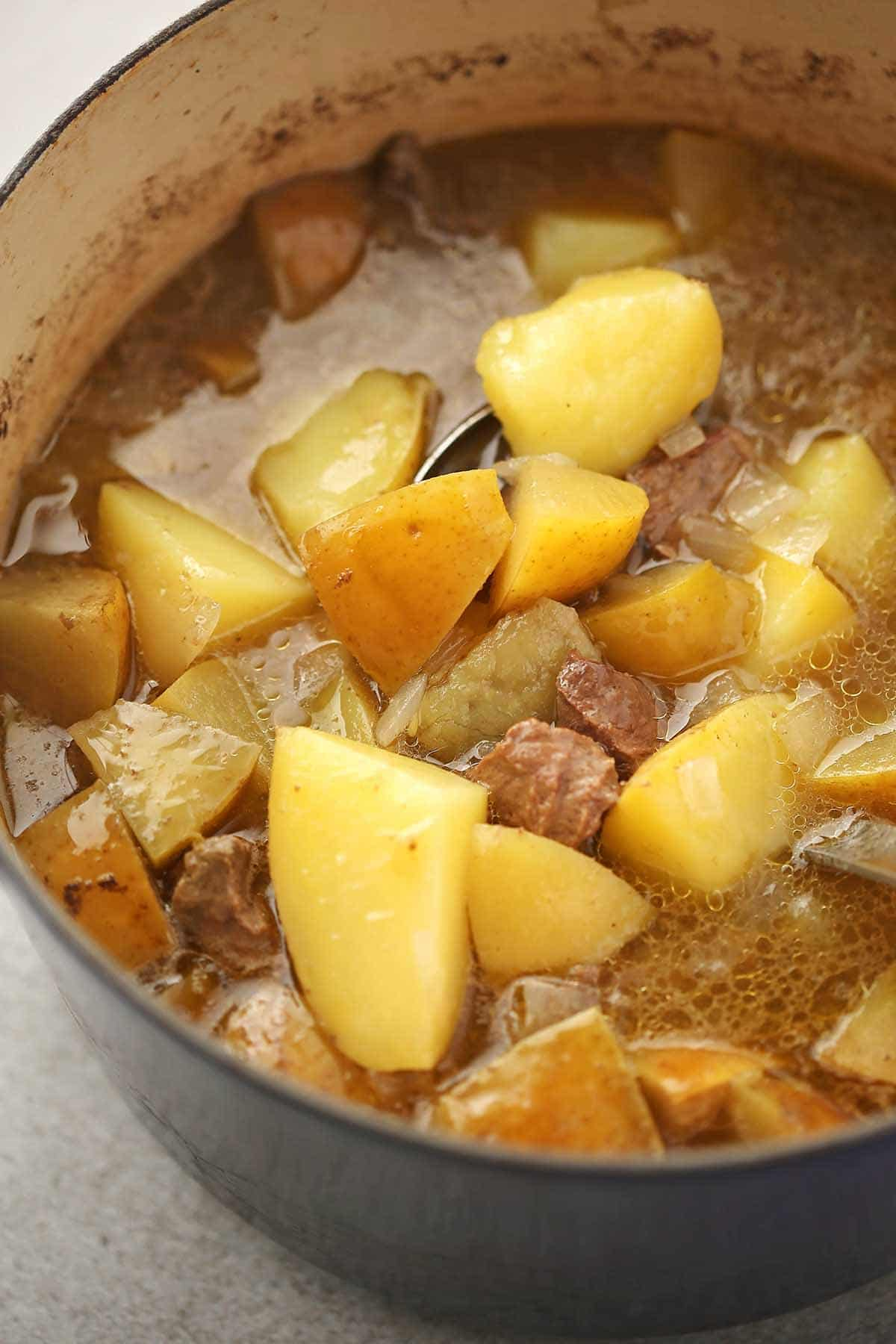 close up shot of the dutch oven pot filled with cooked potatoes, meat and broth