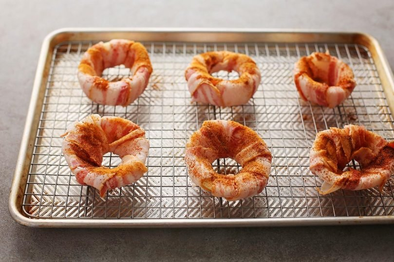 baking sheet pan with round onion rings wrapped in bacon