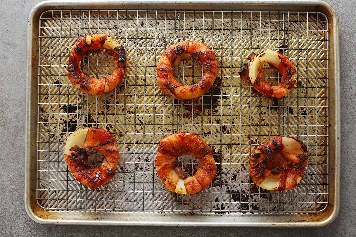 baked browned onion rings on a baking sheet pan