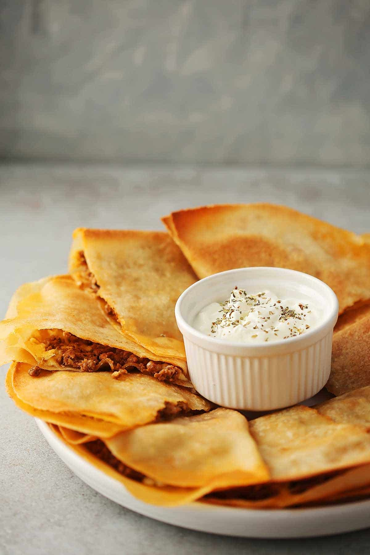 large white plate with sliced quesadillas and small dish filled with dressing