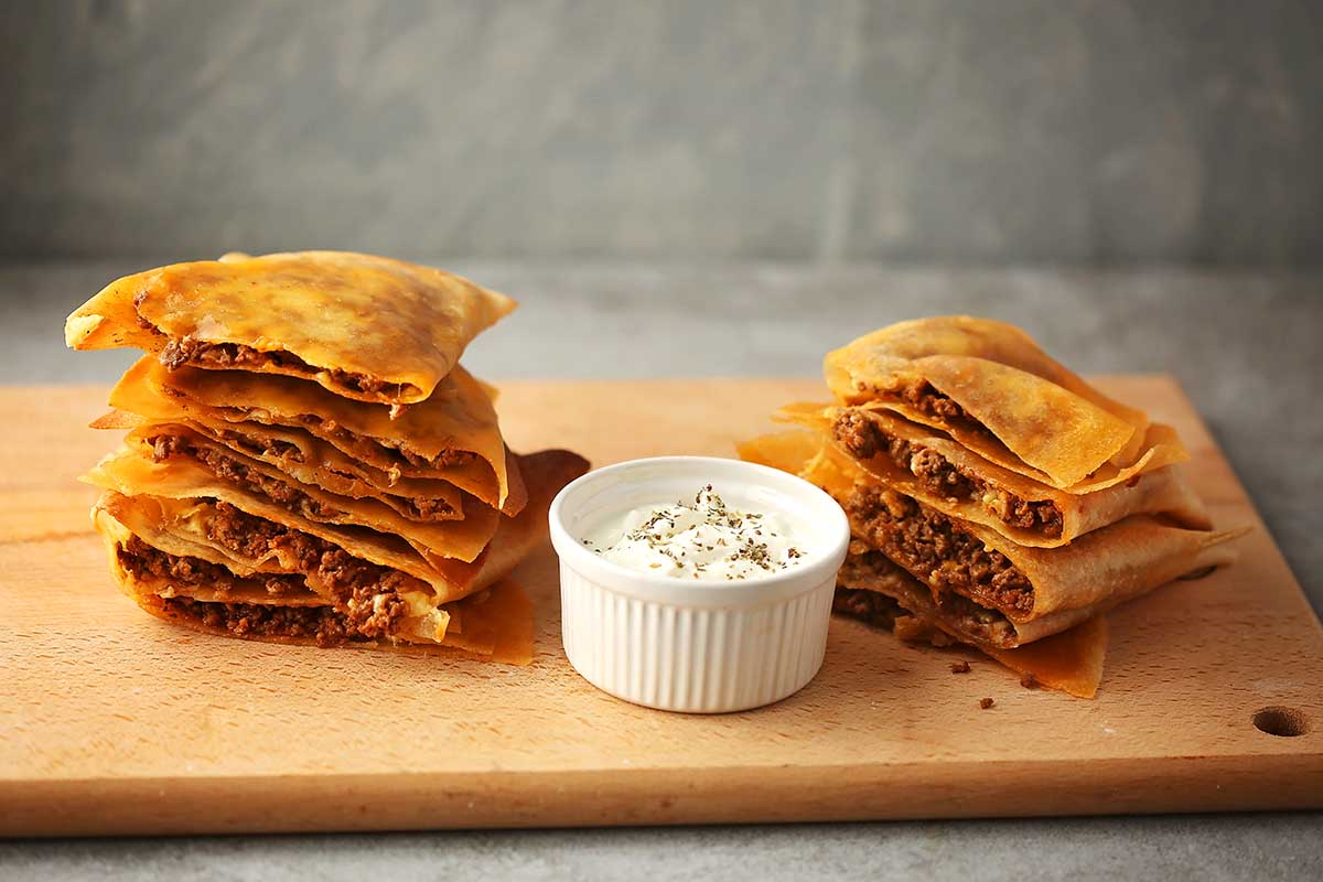 sliced quesadillas on the cutting board with white dressing in the small dish