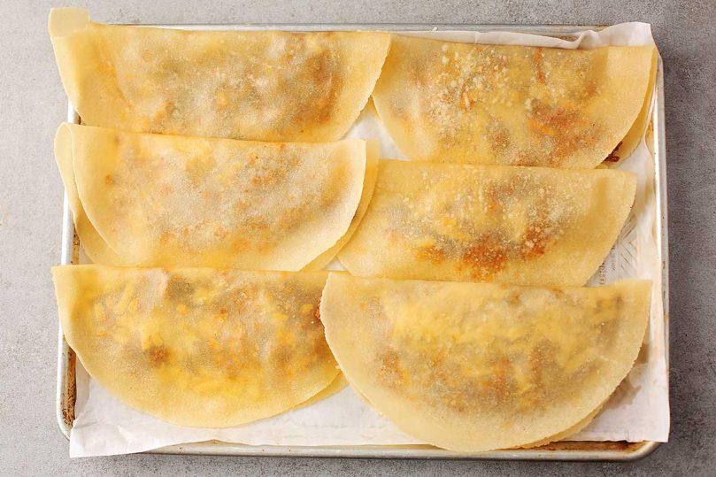 stuffed tortillas arranged inside the baking sheet
