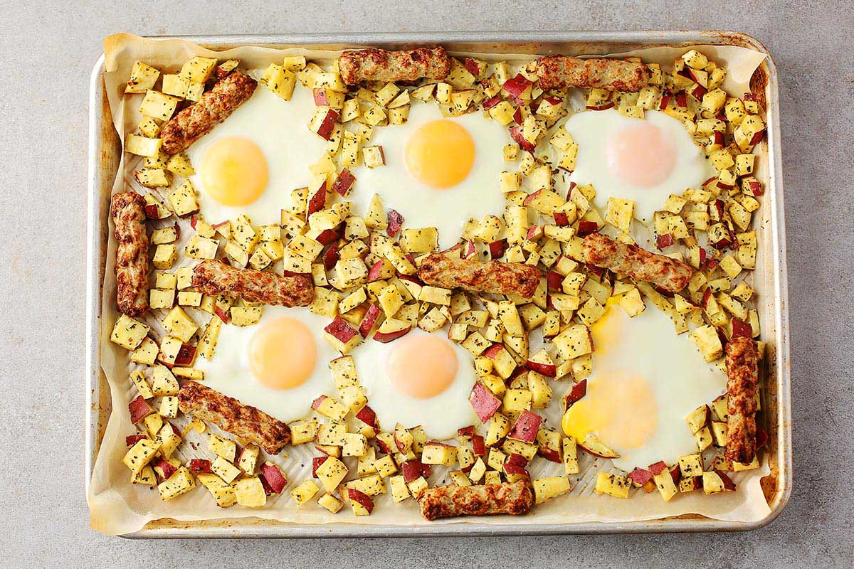sheet pan with baked potatoes, eggs and sausage
