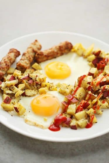 white plate with sunny side up eggs, cubed potatoes with ketchup sauce