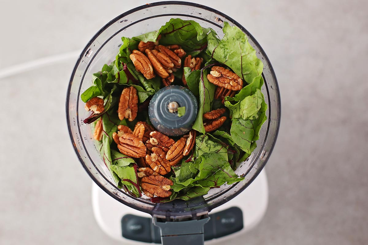 food processor with greens and pecan nuts