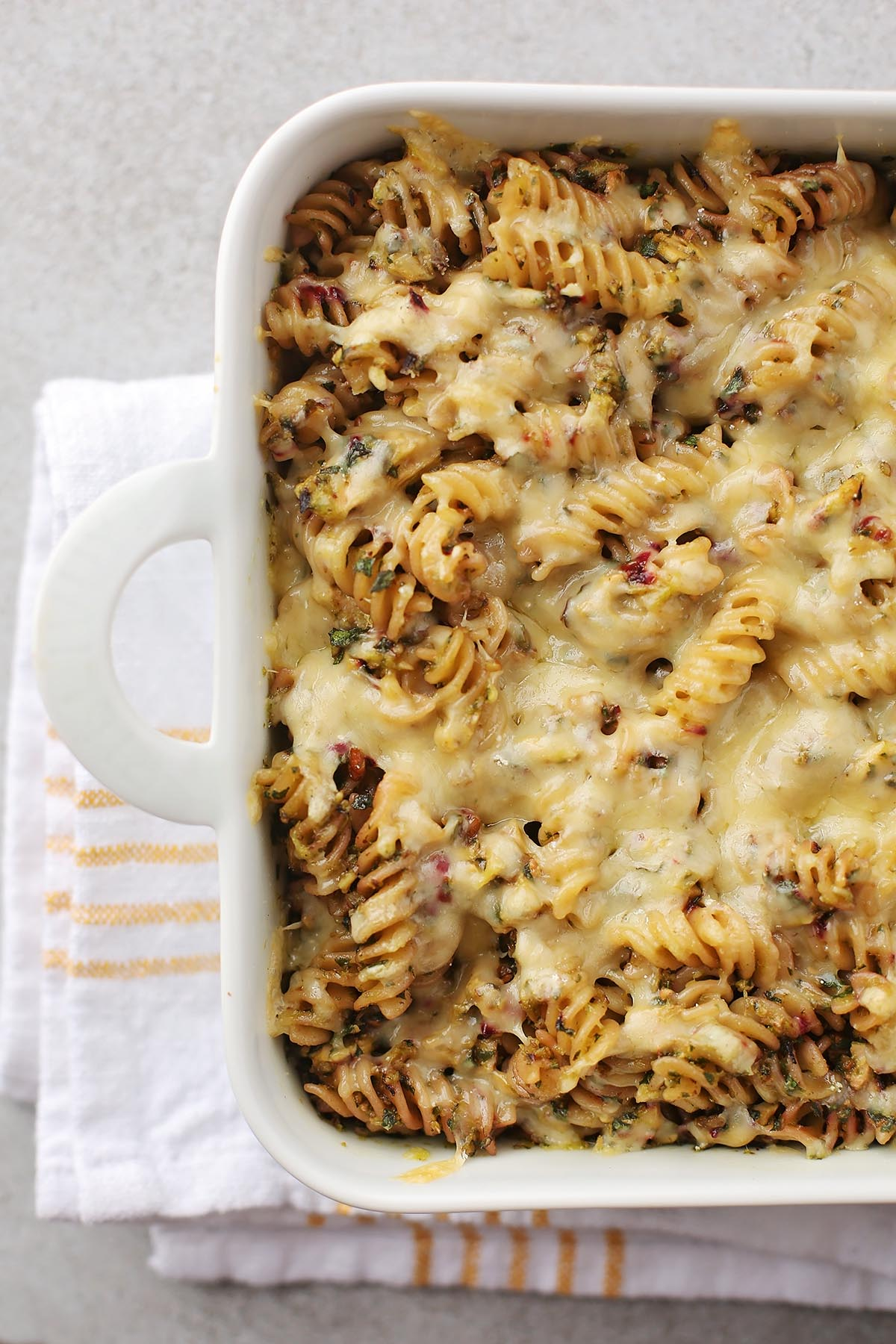 close up shot of cheesy casserole in a white baking dish