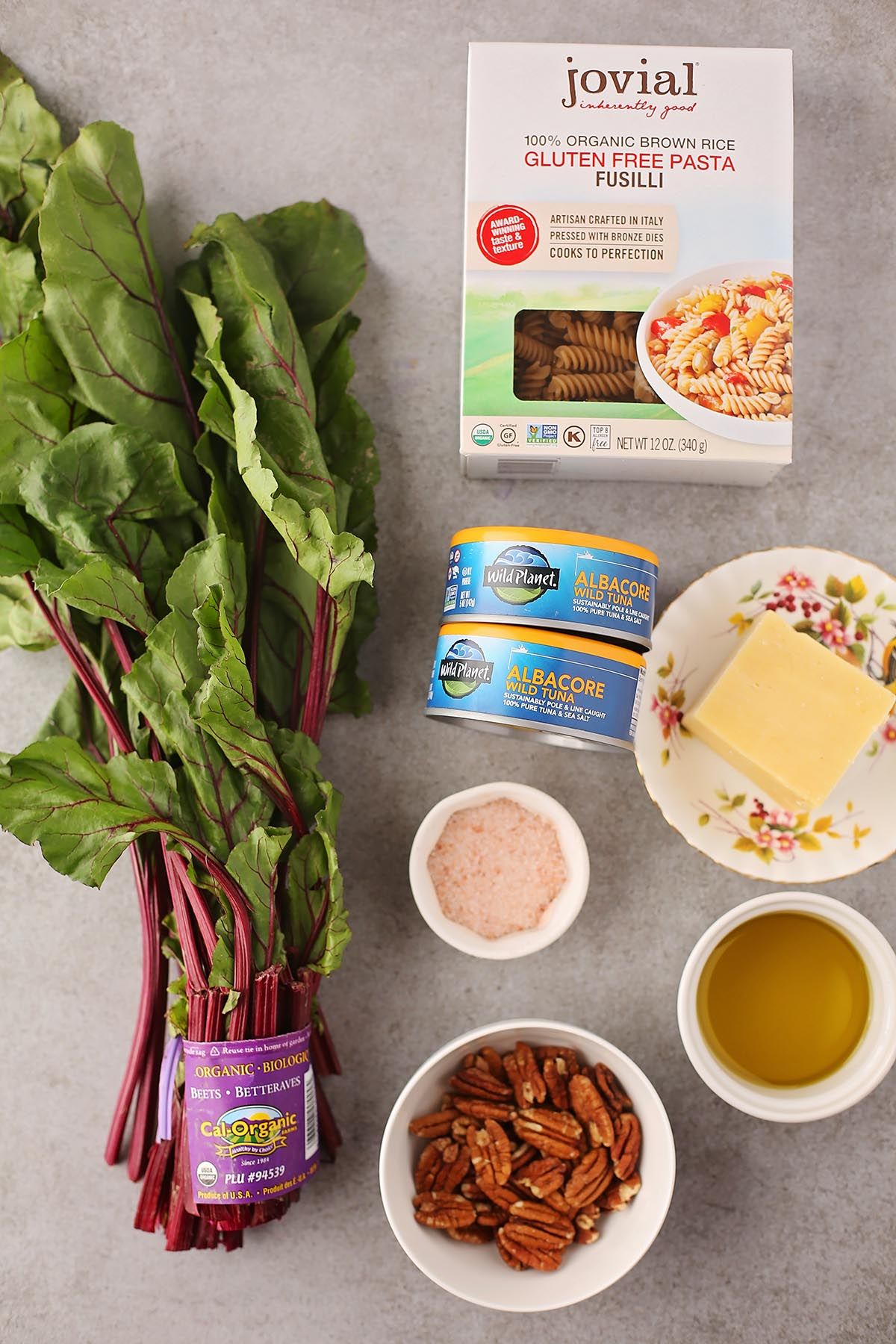 tabletop with beet greens, pecans in the small dish, salt in the dish, canned tuna and package with pasta