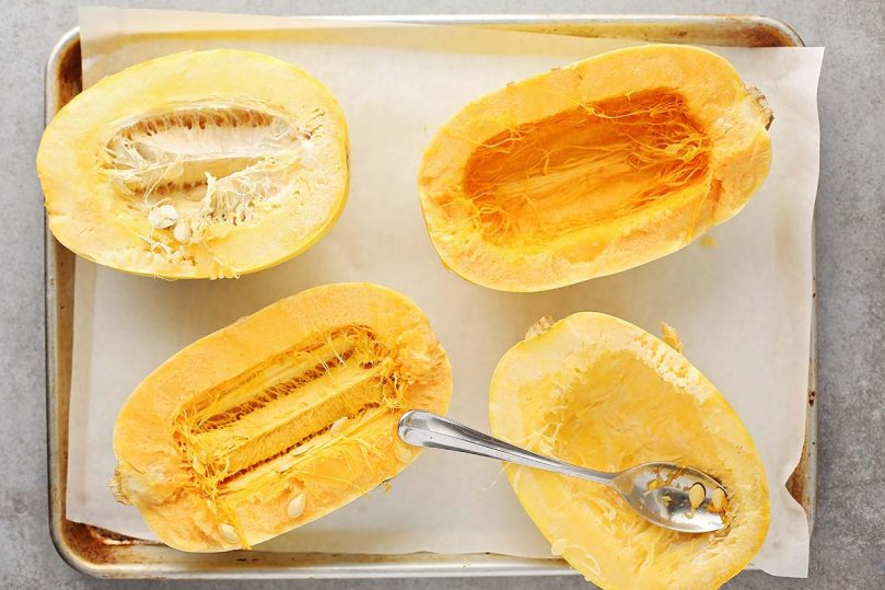 sliced spaghetti squash on top of the baking sheet