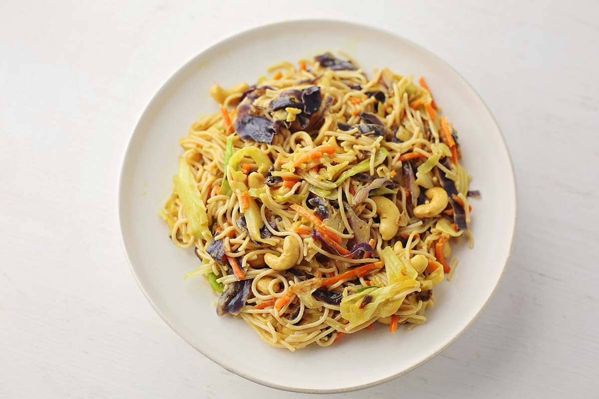 large white plate filled with yellow noodles and cabbage