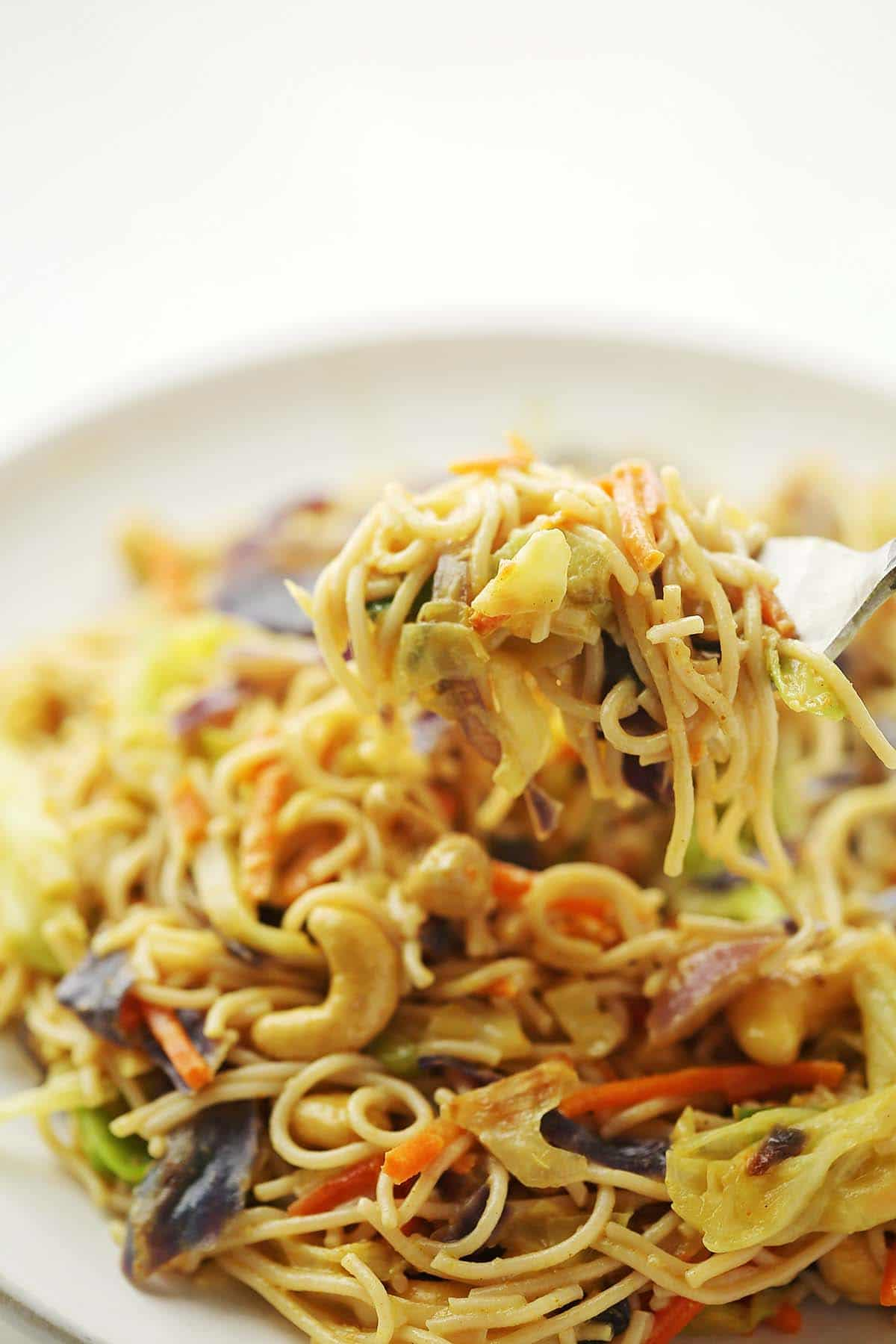 close up shot of plate with cabbage, noodles and cashew nuts
