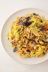 white plate filled with yellow cabbage mix and noodles