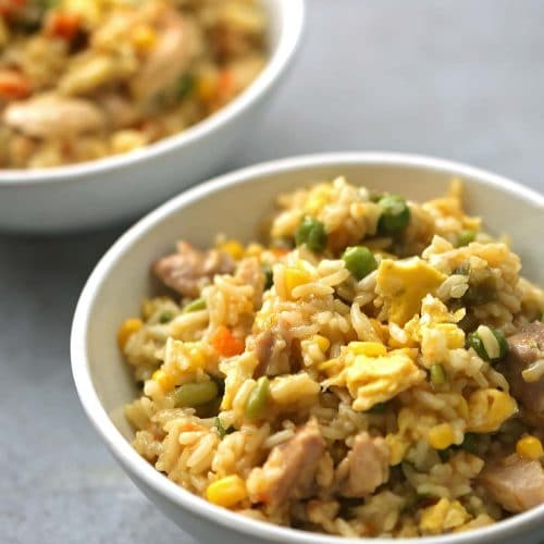two white bowls with fried rice and vegetables