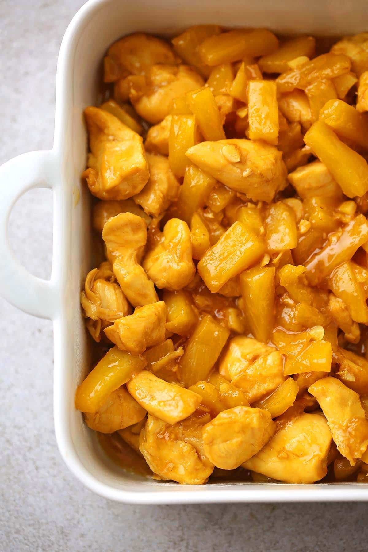 white casserole dish with chicken and pineapple