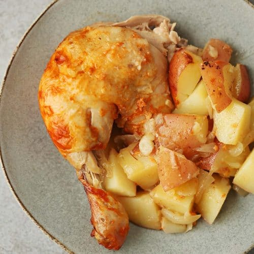 grey plate with roasted chicken leg and potatoes