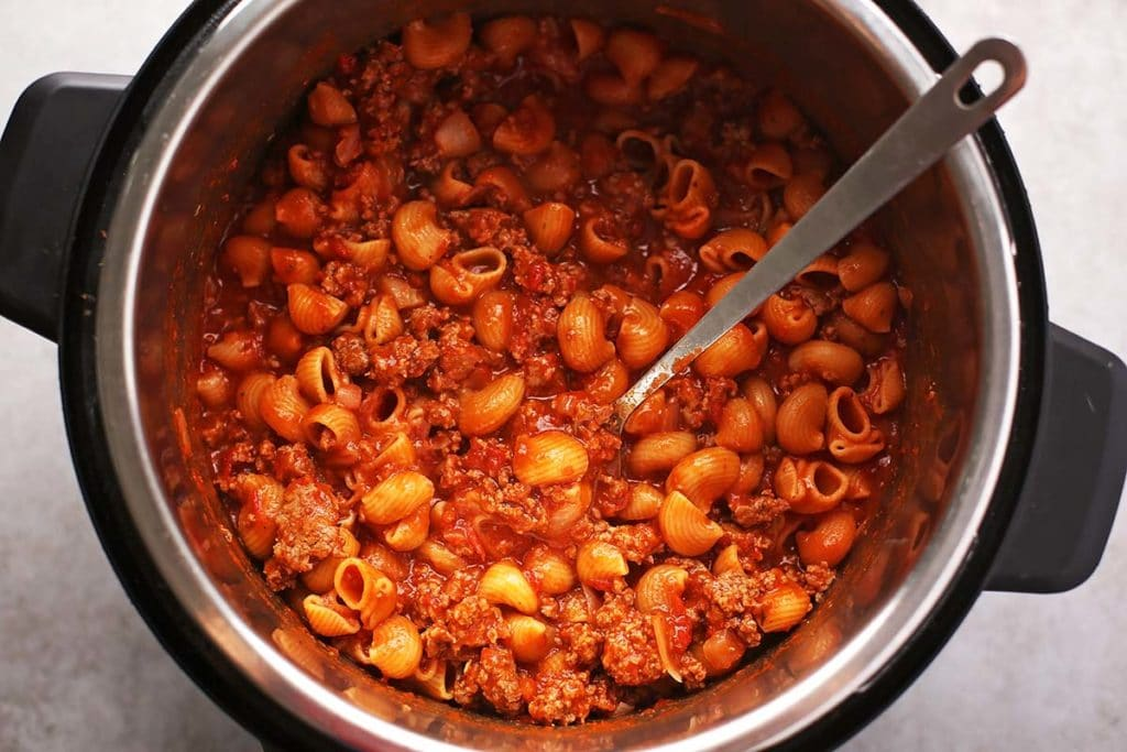 instant pot with cooked meat, pasta and red sauce