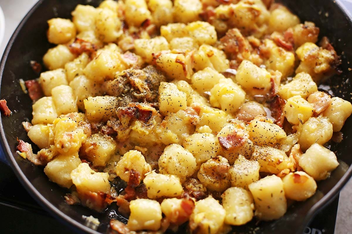 cast iron skillet with cooked bacon and gnocchi