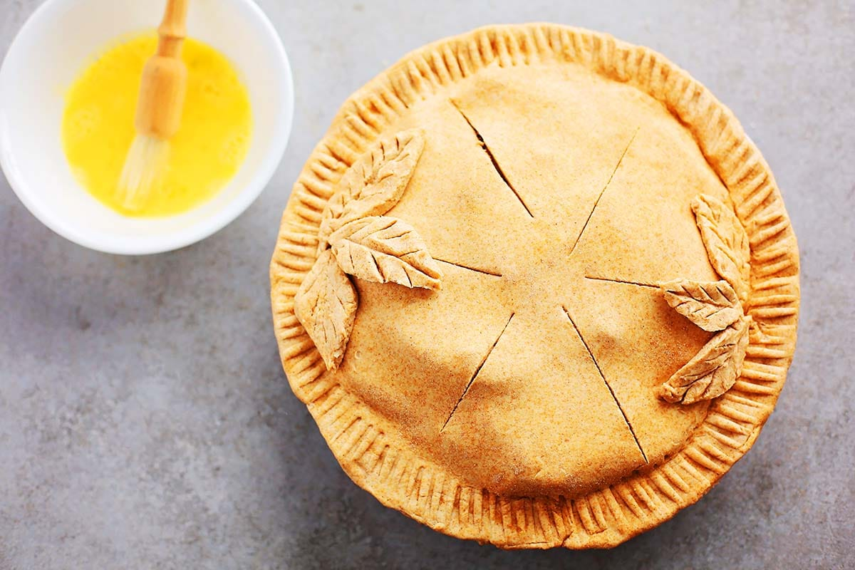 unbaked covered with pastry apple pie decorated with some edible elements