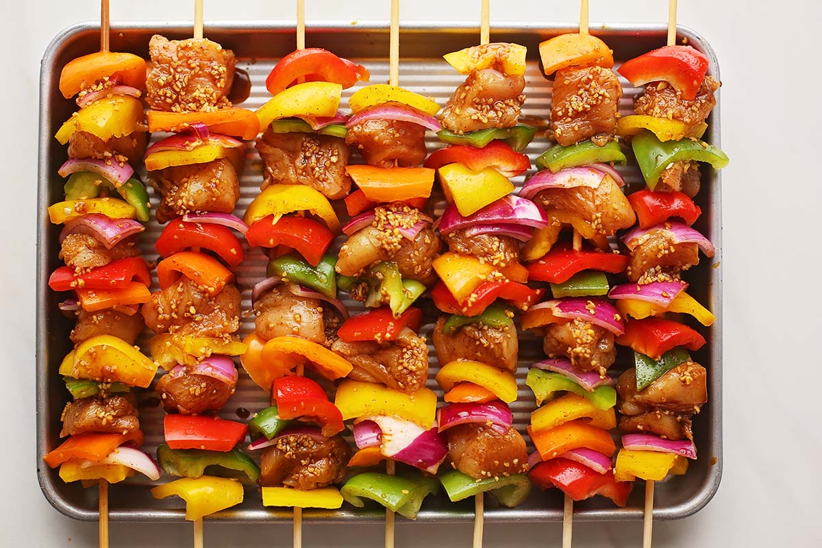sheet pan with uncooked chicken skewers with colorful vegetables