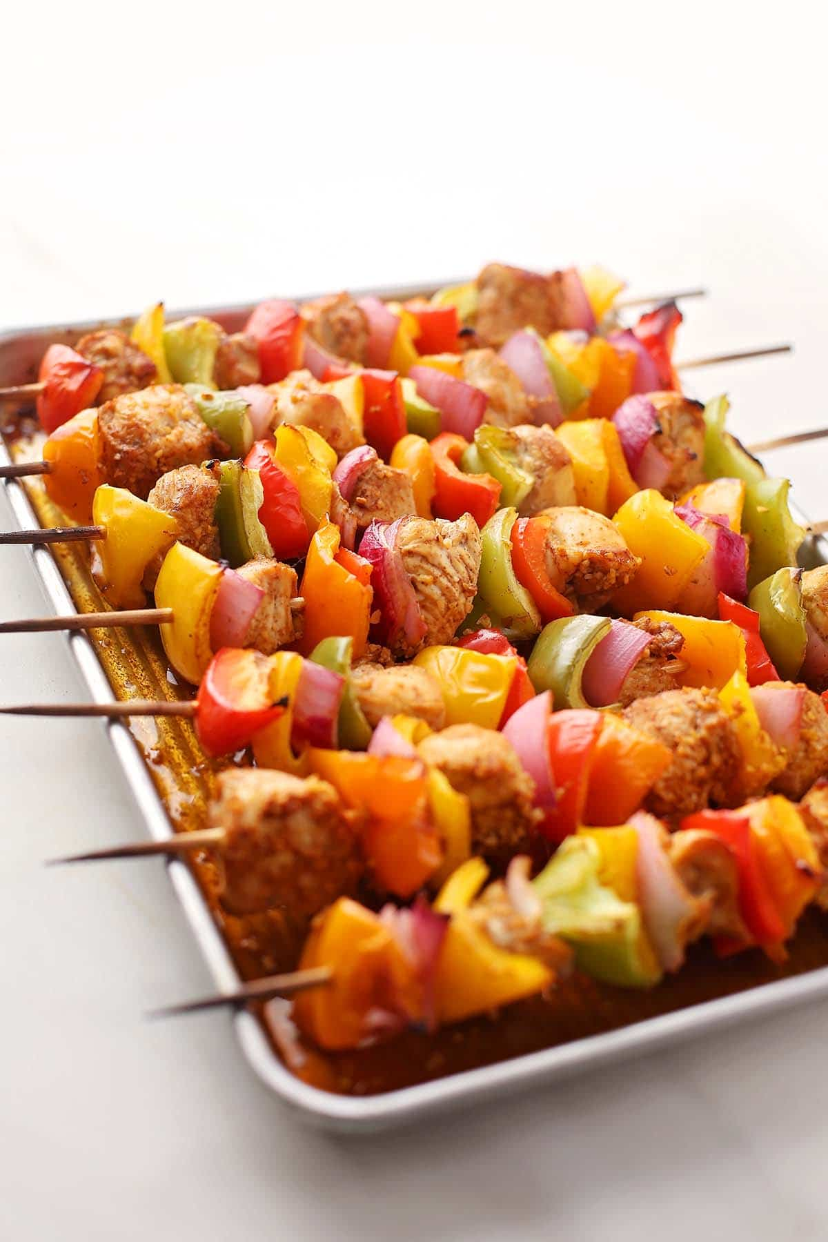 sheet pan with cooked chicken skewers with colorful vegetables