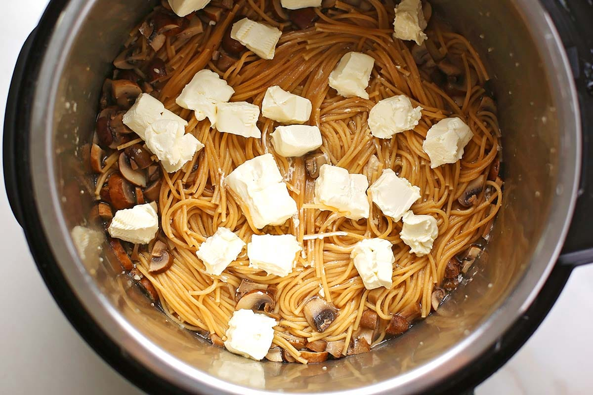 instant pot with spaghetti topped with chunks of cream cheese