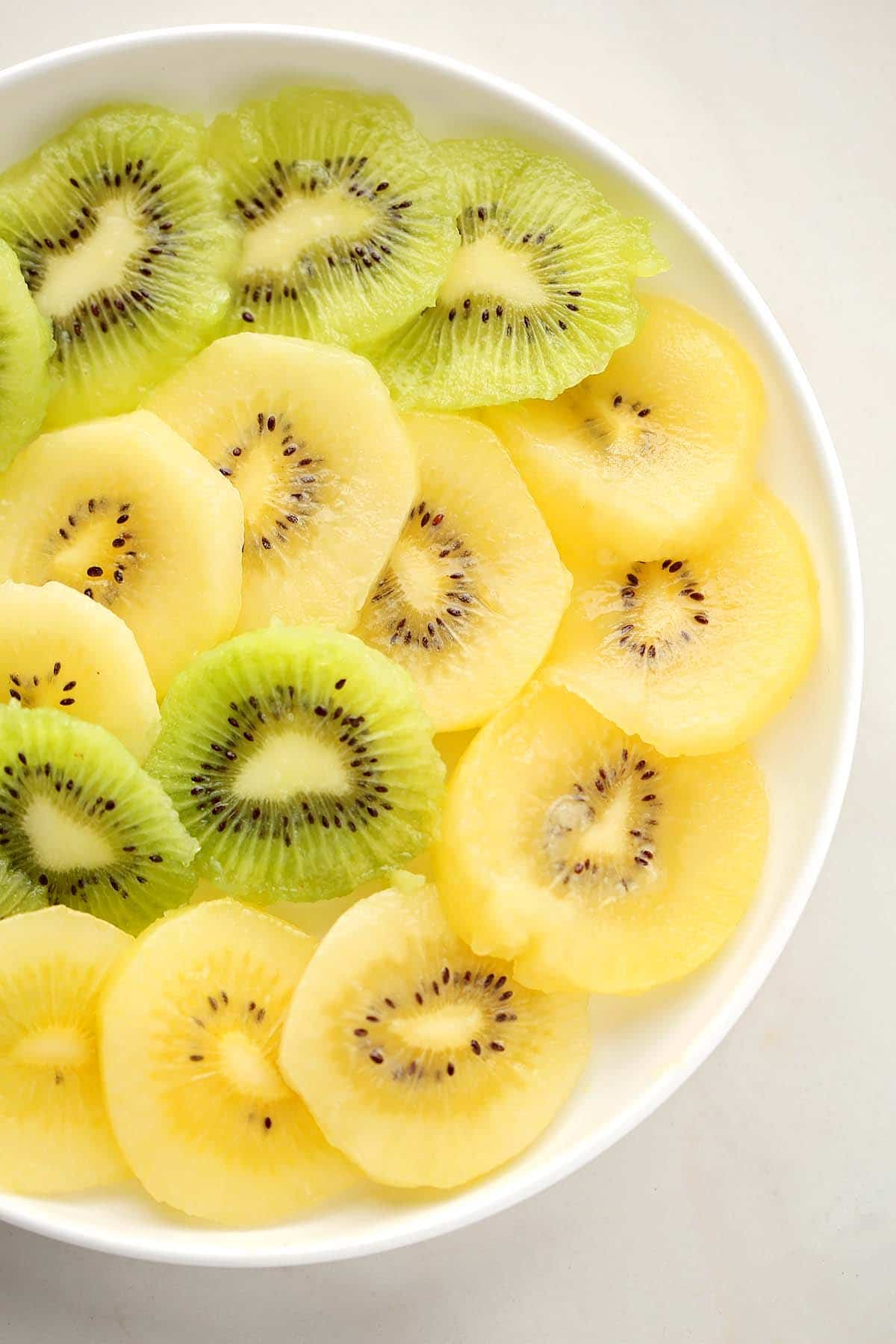 white plate with sliced yellow and green kiwi