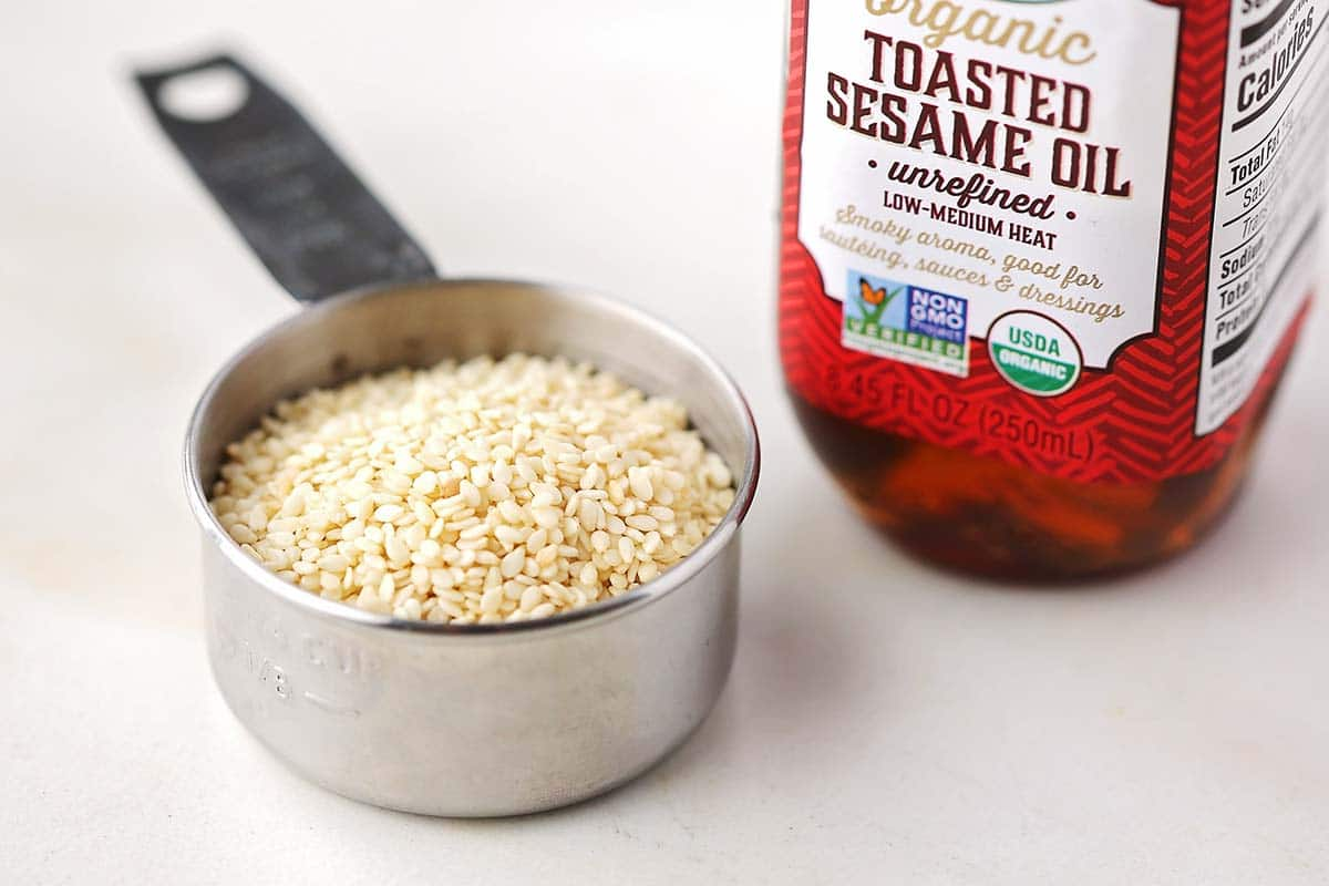 measuring dish filled with sesame seed and bottle with brown colored sesame oil