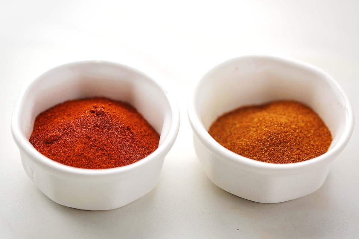 two white small bowls filled with bright orange paprika spice