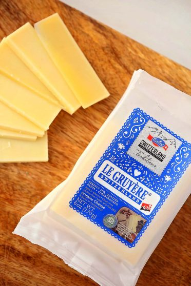 package named Gruyere Cheese, sliced cheese and cutting board
