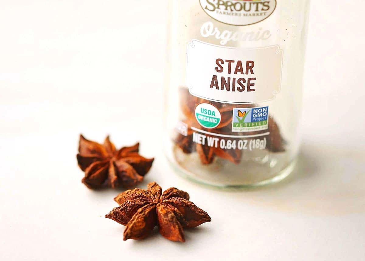 star anise laying on white surface with spice bottle next to it