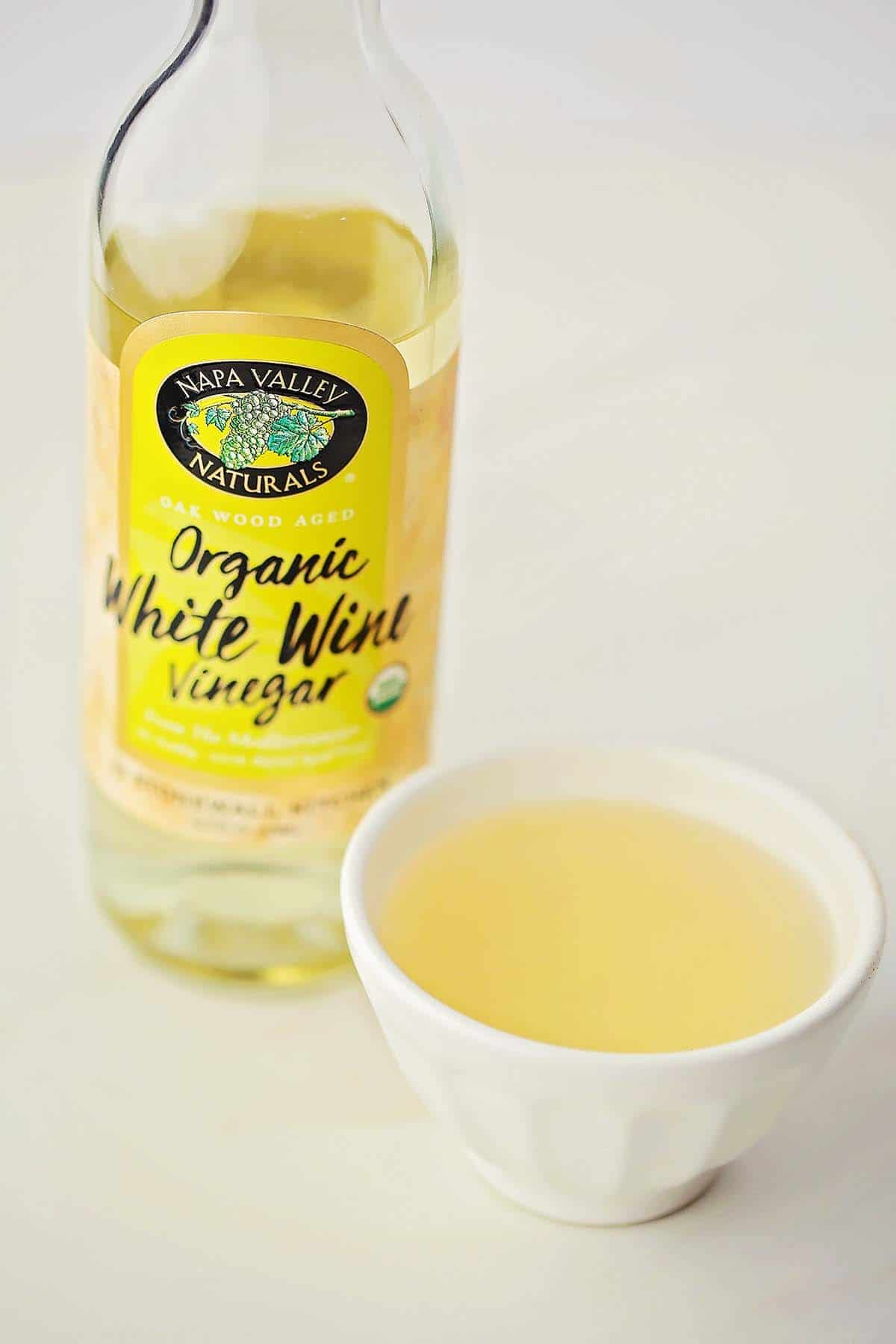 bottle with white wine vinegar and small dish filled with yellow liquid