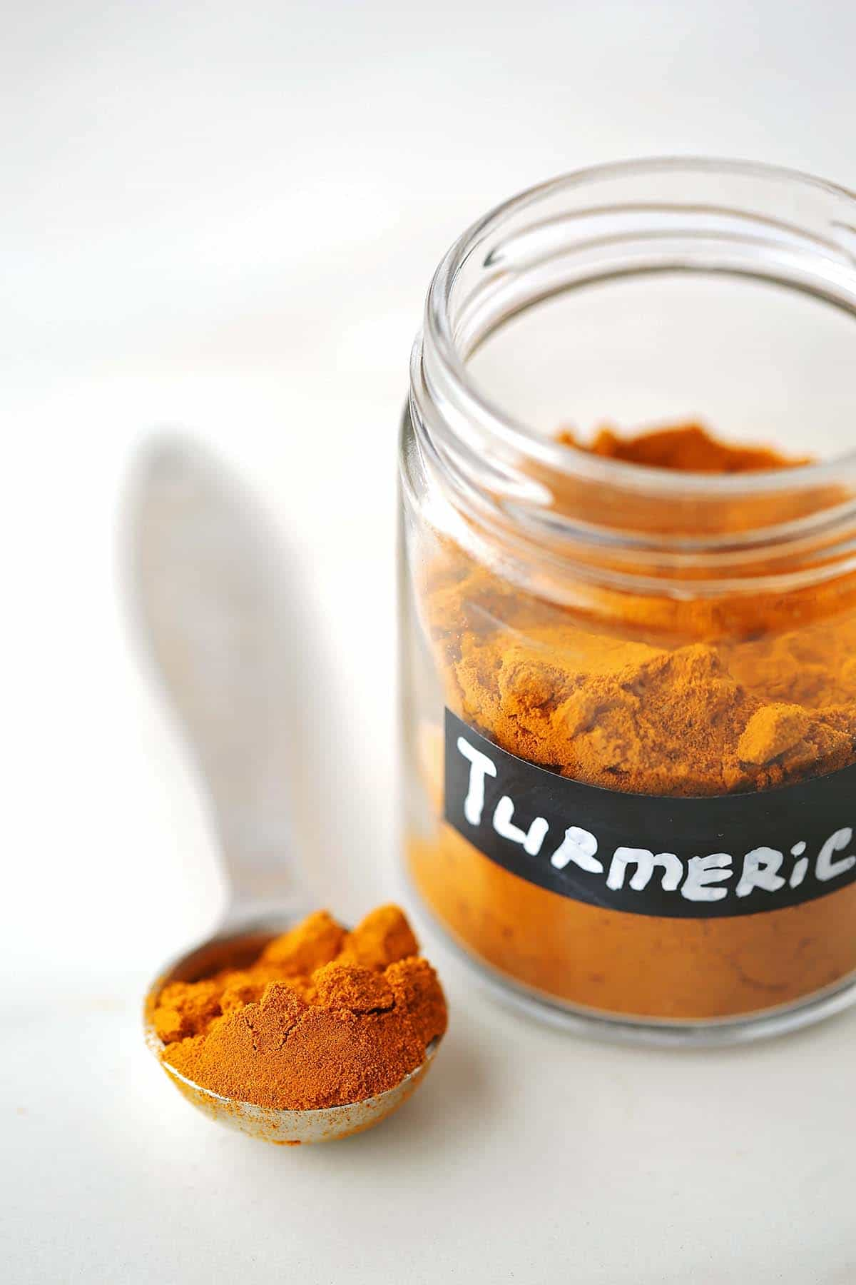 measuring spoon filled with bright orange spice and glass jar filled with spice and labeled turmeric