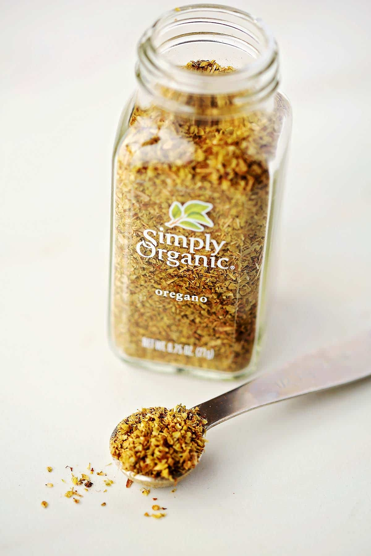 measuring spoon with spice, glass bottle with dry spice labeled Oregano