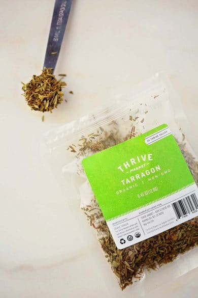open package with tarragon spice and measuring spoon full of dried herbs