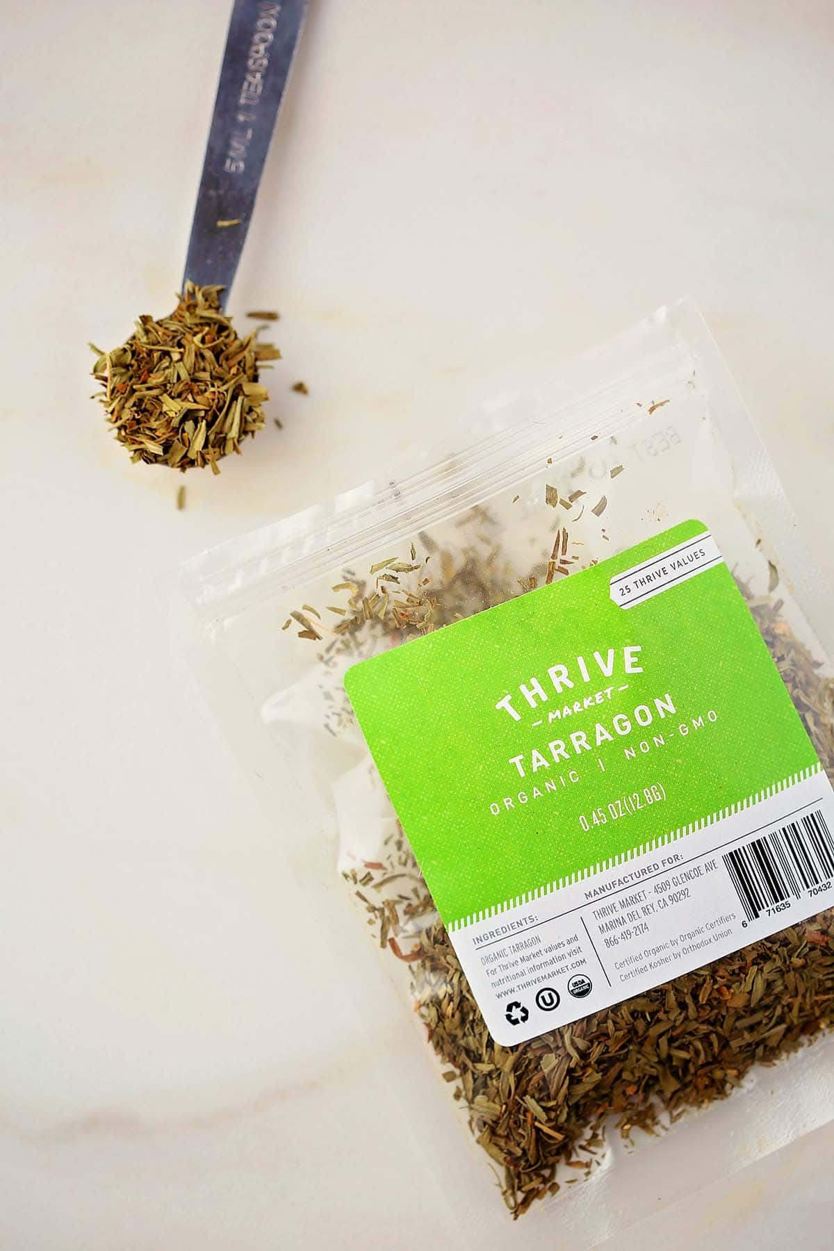 measuring spoon with dried spice and bag labeled tarragon spice